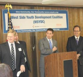 photo of Dr. Wieczorek, Jon Linder and local politicians and community leaders at a podium. Photo was taken durning the coalition kick-off event in 2012